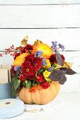 Beautiful autumn composition in pumpkin and box with old letters  on color wooden background