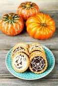 Tasty Halloween cookies on plate, on wooden table