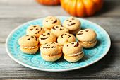 Tasty Halloween macaroons on plate, on wooden table