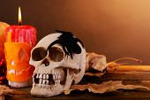 Composition of decorative skull, pumpkin, candles and Halloween decorations on wooden table, on dark color background