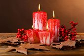 Bloody candles for Halloween holiday, on wooden table, on dark color background
