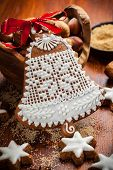 Homemade gingerbread bell for Christmas with baking ingredients