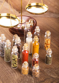 stock photo of vedic  - Little bottles with spices and scales on the table - JPG