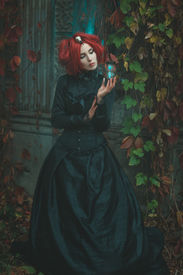 picture of wraith  - Girl with karasnymi hair in ancient dress like a witch standing with hourglass in hand - JPG