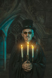 picture of sorcerer  - Evil sorcerer man with a candelabrum in the hands in which candles are burning - JPG