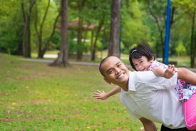 stock photo of southeast  - Father and daughter playing piggyback at outdoor garden park - JPG