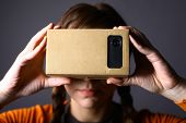 pic of shot glasses  - Color shot of a young woman looking through a cardboard a device with which one can experience virtual reality on a mobile phone - JPG