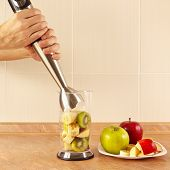 foto of blender  - Hands are going to cook prepare fruit cocktail in a blender - JPG