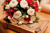 stock photo of ivory  - Close up of wedding ivory and red bouquet