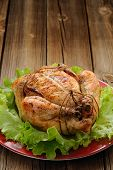 image of bondage  - Bondage shibari roasted chicken with salad leaves on red plate on wooden background with space vertical - JPG