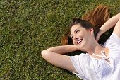 stock photo of rest-in-peace  - Relaxed happy woman resting on the grass looking at side with copy space and a green background - JPG