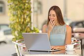 foto of yawn  - Tired woman yawning and working with a laptop in a restaurant during breakfast - JPG