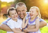 stock photo of father time  - Father with his two children spending time together outside in green nature - JPG