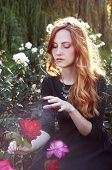 image of auburn  - Young woman with auburn hair casting a spell in the rose garden