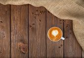 stock photo of whipping  - Cup of cappuccino coffee with heart on the whip at wooden table - JPG