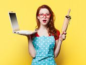 stock photo of plunger  - Housewife with computer and plunger on yellow background - JPG