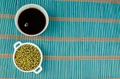 picture of soy sauce  - Bowl with soy sauce and soy beans on a bamboo mat - JPG