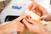 stock photo of manicure  - Manicure in the spa salon. Drawing of red nail polish. Spa manicure, nail care. Girl does a manicure. The concept of hand care. ** Note: Shallow depth of field - JPG