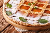 foto of apricot  - Tasty Italian crostata with apricot jam and mint on a wooden table - JPG