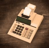 stock photo of subtraction  - Old dirty calculator on a wooden desk  - JPG