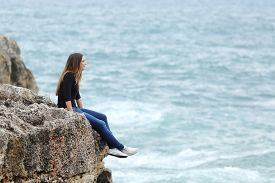 picture of thoughtfulness  - Side view of a full body of a casual woman thinking sitting in a cliff watching the sea - JPG