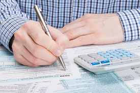 picture of cpa  - Taxpayer filling out 1040 Tax Form  - JPG