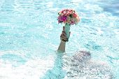 picture of chrysanthemum  - Male in swimming pool with blue water holding beautiful fresh wedding bunch of pink lilac purple white and violet chrysanthemum rose and peony flowers in hand copyspace horizontal picture - JPG