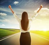 picture of up-skirt  - back view of happy woman raising hands up over road - JPG