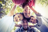 stock photo of huddle  - Happy family in the park huddling in circle on a sunny day - JPG
