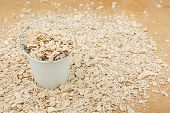 stock photo of bucket  - White bucket with oat flakes on the wooden floor as a background - JPG