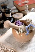 foto of roughage  - Old book with dry flowers in mortar and bottles on table close up - JPG
