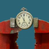 picture of tights  - A vice is tightly pressing an antique pocket watch - JPG
