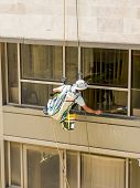 picture of window washing  - Professional window washer cleaning windows on a building - JPG
