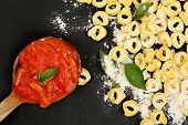 picture of ladle  - raw tortellini pasta and ladle with sauce on black surface - JPG