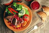 foto of deer meat  - Tasty roasted meat with cranberry sauce - JPG