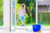 stock photo of window washing  - Little girl washing a window - JPG