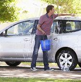 stock photo of car carrier  - Man Washing Car In Drive - JPG