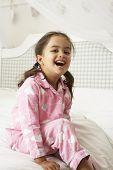 pic of pajamas  - Young Girl Wearing Pajamas Sitting On Bed - JPG