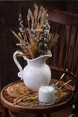 stock photo of willow  - Light morning meal with milk and fresh bread and a bouquet from cones and a willow - JPG