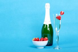 picture of homogeneous  - Glass with champagne and strawberries slices beside bottle of champagne and a bowl of strawberries on a blue background side view - JPG