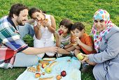 Muslim family, mother and father with three children together in nature sitting and eating on green
