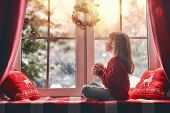 Merry Christmas and happy holidays! Cute little girl sitting by the window with a cup of hot drink a poster