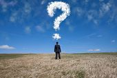 businessman standing alone at the field with a lot of questions in his mind
