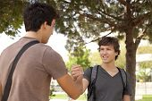 stock photo of young men  - Happy young student giving a handshake to his classmate  - JPG