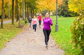 Four Young Woman Out Running Together In A Park poster