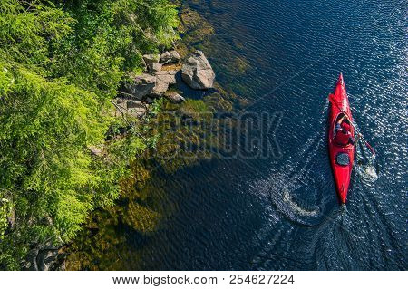 poster of River Kayaker Aerial View. Caucasian Sportsman In The Red Kayak Paddling On The Scenic River Along T
