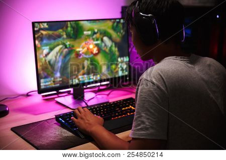 poster of Photo of teenage gamer boy playing video games on computer in dark room wearing headphones and using
