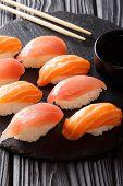 Постер, плакат: Sushi Set With Salmon And Tuna Soy Sauce Close up On A Black Slate Vertical
