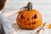 Woman Carving Big Orange Pumpkin Into Jack-o-lantern For Halloween Holiday Decoration On White Woode poster