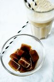 Frothy Ice Coffee In Glass With Drinking Straw And Coffee Ice Cubes On White Background, Vertical Cl poster
